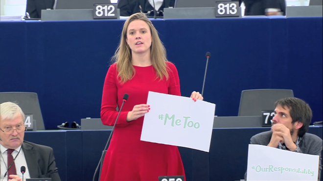 European Parliament member in red dress holding placard that says MeToo.