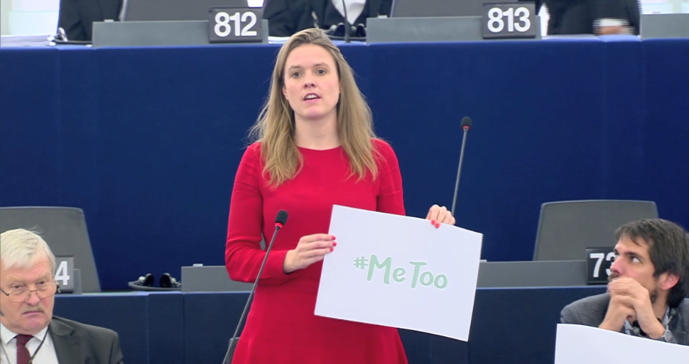 Women in red dress holding a #MeToo sign in the European Parliament