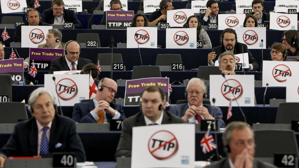 Meetin in European parliament, MEPs with plaquets with anti-TTIP signs