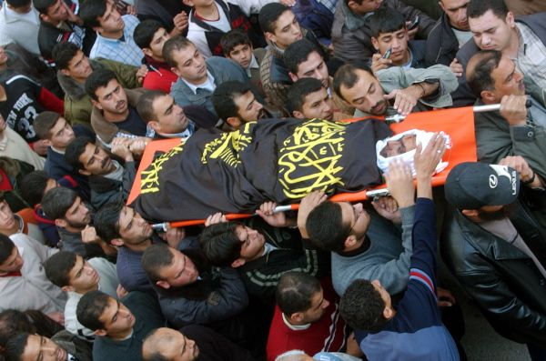 Group of people carrying the body in a burial march.