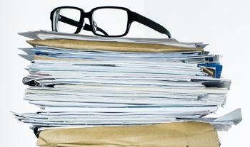 pile of documents with glasses on top