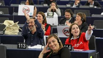 Seats with EU Parliament members with anti-TTIP signs and T-shirts