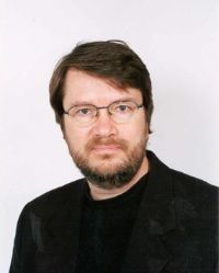 Man wearing black with glasses and beard.