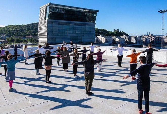 People doing excercises on the roof top of the Oslo Opera House