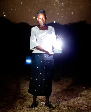 Woman in Ikisaya village in Kenya using a portable solar lantern