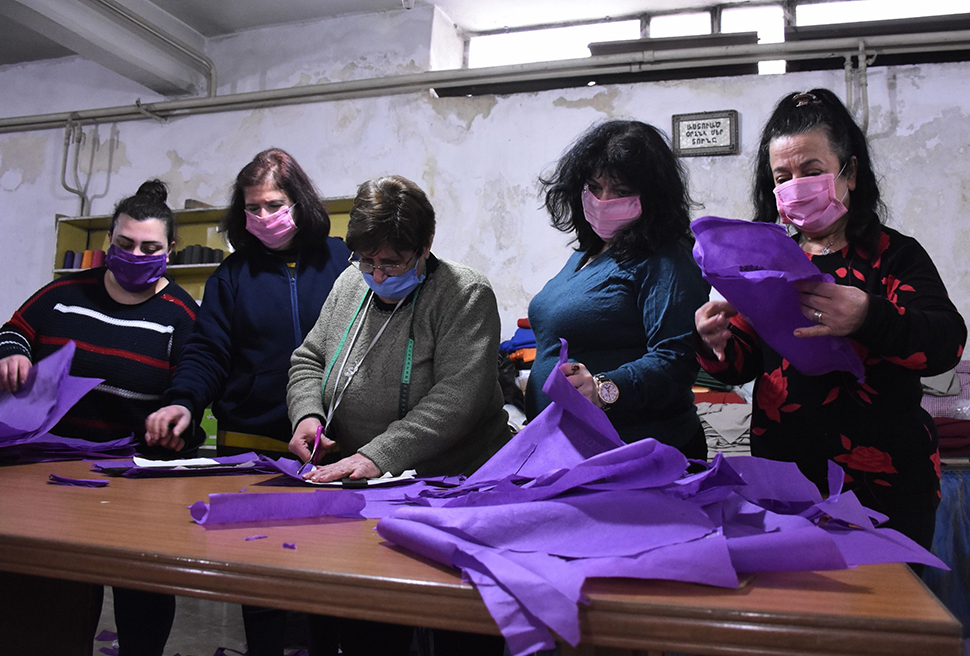 Women with masks against viruses are sewing