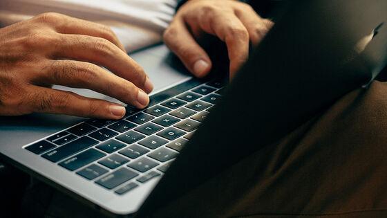 Nærbilde av hender som skriver på tastaturet på en laptop