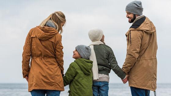 Foreldre med to barn holder hverandre i hendene, og de to barna ser opp på hver sin forelder
