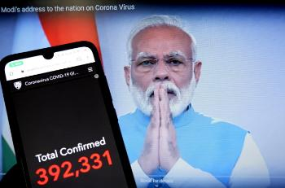 Inder med hender mot hverandre ved siden av et bilde fra en mobil som viser antall koronatilfeller