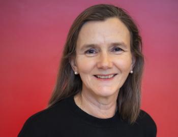 Kvinne med langt, brun hår, smilende ansikt, rød bakgrunn