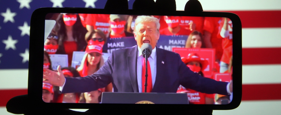 The president Donal Trump holding a speech, shown through a camera on a mobilephone
