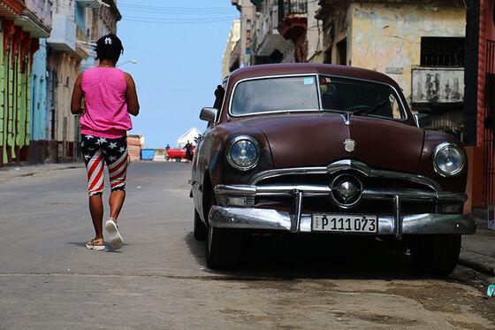 Kubansk kvinne med amerikatights passerer gammel bil på gata