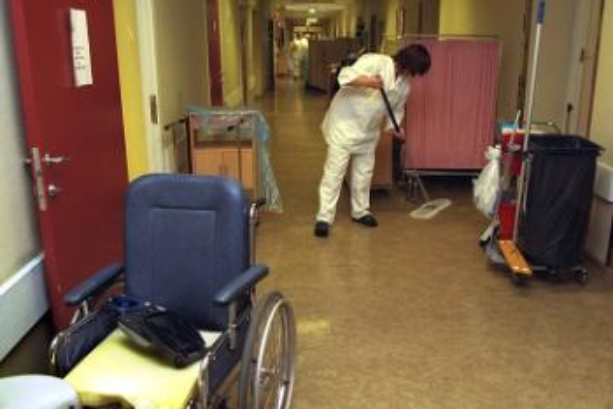 Ullevål sykehus. En rullestol i forgrunnen. Rengjøring av en korridor.