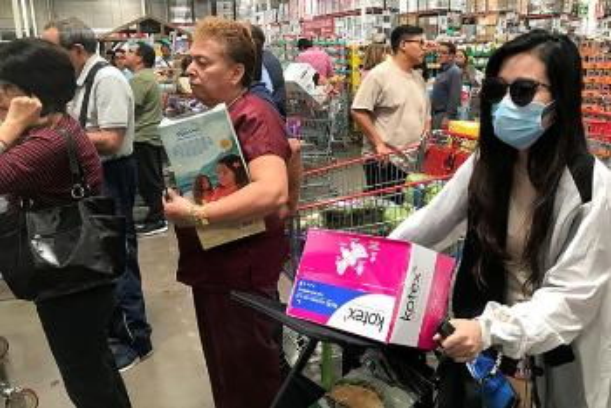 Kvinne med munnbind triller barnevogn full av varer