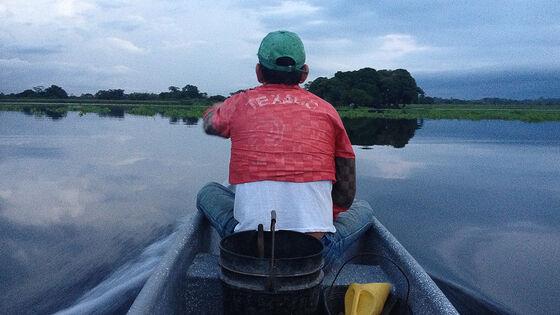 Mann som fisker fra liten båt.