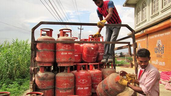 To nepalere losser gasstanker av en lastebil.